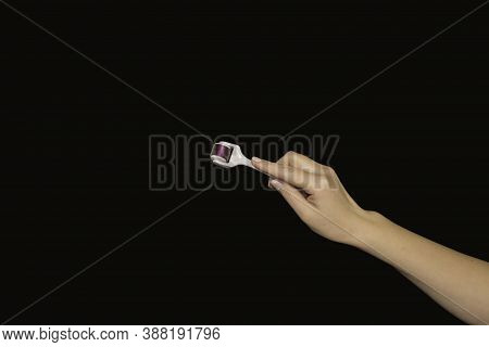 Hand And Mesoroller In Hand On A Black Background. Scalp And Skin Care, Healthy Hair.