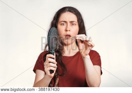 Portrait In A Blur, A Frightened Brunette Woman Holds A Comb In Her Hands, Clearing It From A Pile O