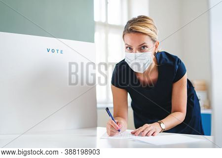 Portrait Of Woman Voter With Face Mask In Polling Place, Usa Elections And Coronavirus Concept.