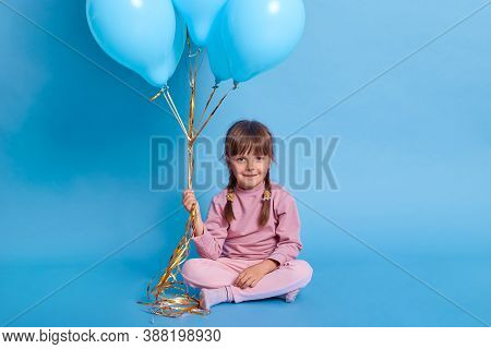 Dark Haired Female Child With Pigtails Sitting On Floor With Crossed Legs, Looks At Camera, Holding