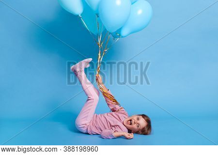Little Toddler Girl Having Fun While Lying On Floor With Raised Legs, Looks At Camera And Yelling Ha