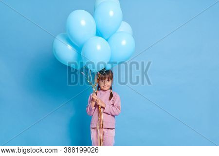 Charming Small Girl Looks Attentively At Camera, Holding Bunch Of Helium Balloons, Wears Pink Jumper
