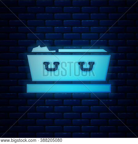 Glowing Neon Open Coffin With Dead Deceased Body Icon Isolated On Brick Wall Background. Funeral Aft