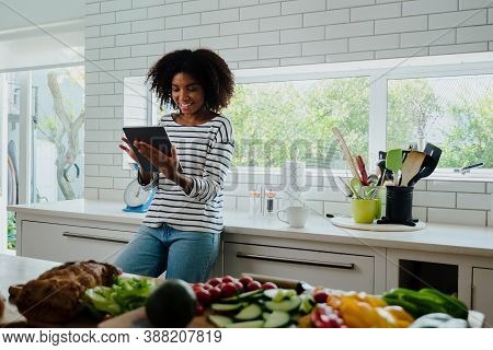 African American Smiling Female Researching Recipes On Digital Tablet Leaning Against Counter In Cle