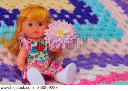 Doll With A Flower Sitting, Little Toy Doll Sitting On A Colored Plaid