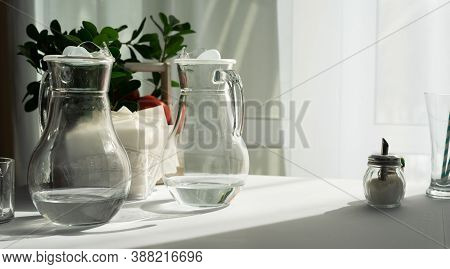 Two Clear Glass Decanters Of Water On A Table With A White Tablecloth In The Morning Sun.