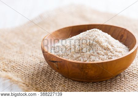 Heap of psyllium husk in wooden bowl on wooden table table. Psyllium husk also called isabgol is fiber derived from the seeds of Plantago ovata plant found in India.