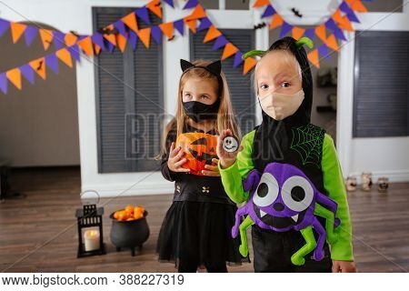 Children In Halloween Costumes And With Masks On Their Faces Play A Trick Or Treat . Children Have F