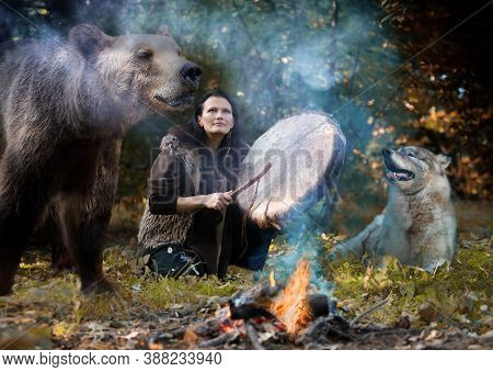 Female Shaman Playing Her Shaman Sacred Drum In The Forest Among Wild Animals - A Dog And A Bear. Th