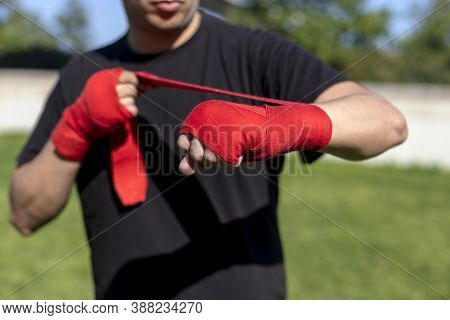 Boxer Preparing For Training With Forearm Bandage Outdoors