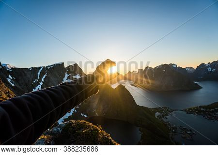 Hand Reaching Out For Midnight Sun In Norway. The Sun Doesnt Set During Summer Months In Norway And