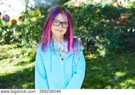 Beautiful Portrait Of A Girl 8 Years Old With Pink Hair In The Garden In Summer.