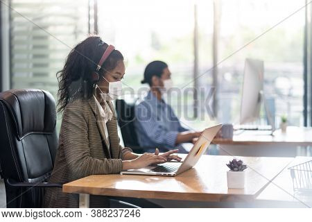 Mixed race of African black and asian businesswoman office worker wear face mask working in new normal office with social distance to colleague in background prevent coronavirus COVID-19 spreading.