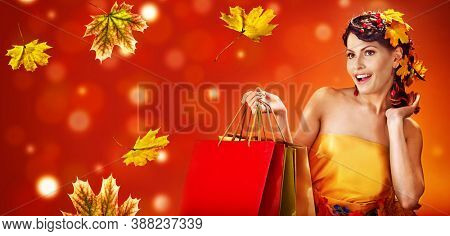 Autumn sale shopping bag banners maple leaves background with beautiful woman. Fashion dream in red fall color outside.