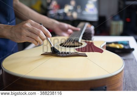Acoustic Guitar Care, Craftsman Is Cleaning The Guitar With Cleaning Brush, Close Up.