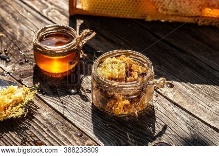 Beekeeping Concept. Jar Of Fresh Honey In A Glass Jar, Beekeeping Tools Outside. Frame With Bees Wax