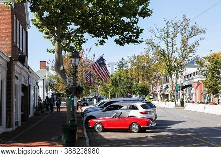 NEW CANAAN, CT, USA - OCTOBER 4, 2020: Downtown in nice day with store fronts and restaurant and blue sky on Elm Street.