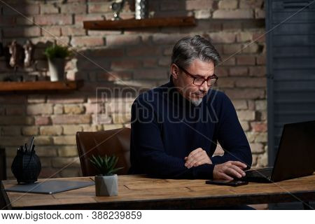 Smart looking older business man working in home office using laptop computer.