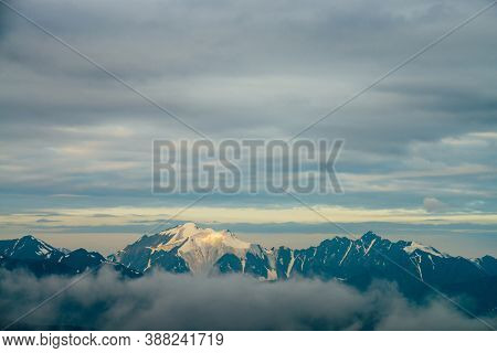 Atmospheric Alpine Landscape With Big Snowy Mountains Among Low Clouds In Golden Hour. Wonderful Hig