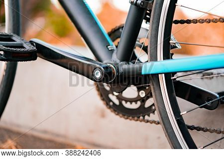 Close-up Of Crank For Bicycle Pedals With Blurred Background. Crankset. Cogwheels. Frame. Chain. Tra