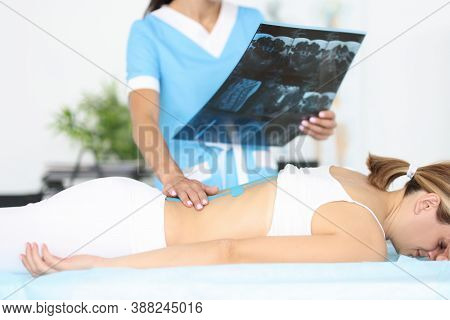 Neurologist Holds X-ray Of Spine In His Hand In Front Of Young Woman Lying On Couch With Blue Kinesi