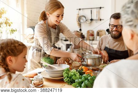 Positive Young Housewife With Little Daughters, Husband And Grandmother Gathering Around Kitchen Tab