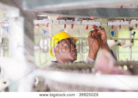 african american blue collar worker working in textile factory