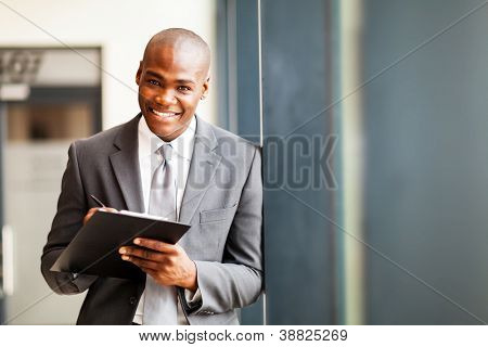 african american businessman writing report in office