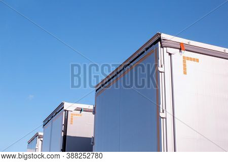 Isotherm Cargo Semi-trailers On A Background Of Blue Sky. The Concept Of The Capacity And Volume Of