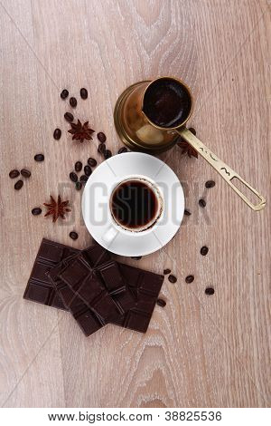 sweet hot drink : black Turkish coffee in small white mug with coffee beans spilled on a wooden table with stripes of dark chocolate and copper Arab Cezve full coffee