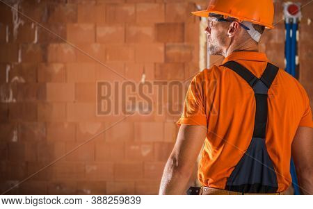 Caucasian Construction Industry Worker In His 40s Wearing Orange Hard Hat And Safety Glasses Prepari