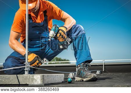 Caucasian Technician Worker Finishing Wires Installation On Building, Part Of Roof Of Lightning Prot