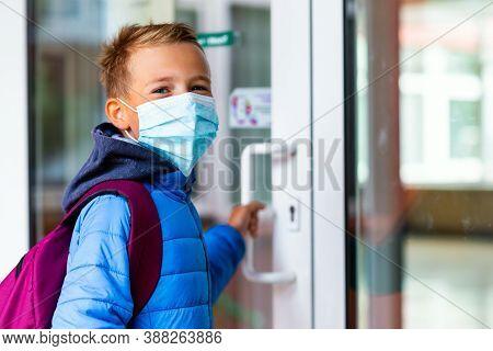 Young Schoolboy Wearing Protective Mask Is Trying To Open The School Door. Behind The Backpack Schoo