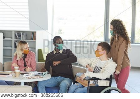Side View At Multi-ethnic Group Of Students Wearing Masks While Studying In College Library With You