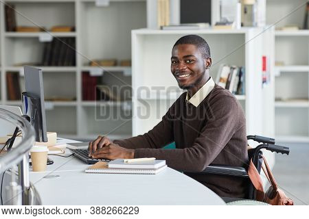 Portrait Of Disabled African-american Man Using Computer And Smiling At Camera While Studying In Col