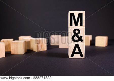 Merger And Acquisition. Text On Wood Cubes. On Black Background