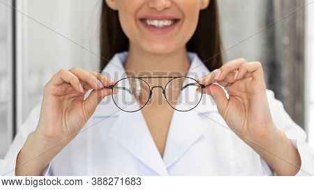 Eyesight And Vision Concept. Closeup Of Unrecognizable Happy Woman Doctor Showing New Eyeglasses At