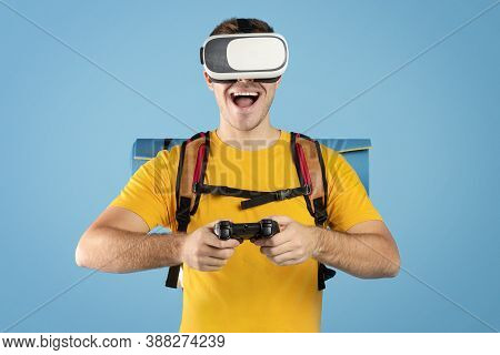 Virtual Tourism. Excited Millennial Guy With Vr Headset And Controller Watching Travel Tour In Cyber