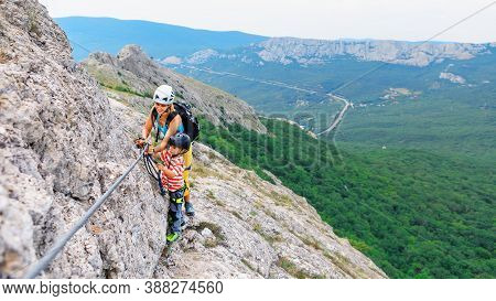 Young Mother, Child In Safety Equipment Climb To Mount Top By Via Ferrata Beginner Route. Family Tra