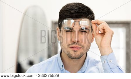 Poor Eyesight Concept. Portrait Of Handsome Young Man With Spectacles Squinting, Trying To Look Clos