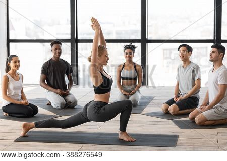 Professional Yoga Instructor Woman Showing Different Asanas To Group Lesson Members In Modern Studio