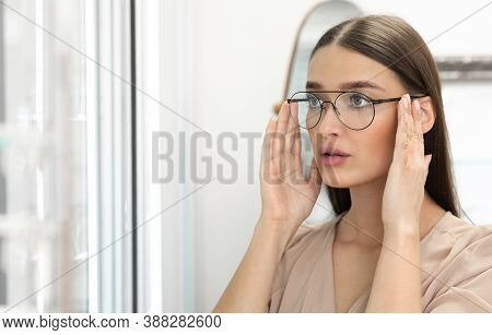Choosing Glasses Concept. Portrait Of Beautiful Lady Picking New Eyewear At Optics Store, Looking At