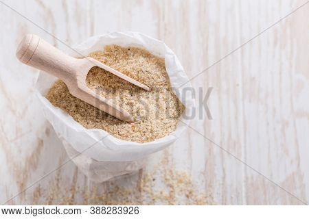 Heap of psyllium husk in small bag on wooden table table. Psyllium husk also called isabgol is fiber derived from the seeds of Plantago ovata plant found in India.