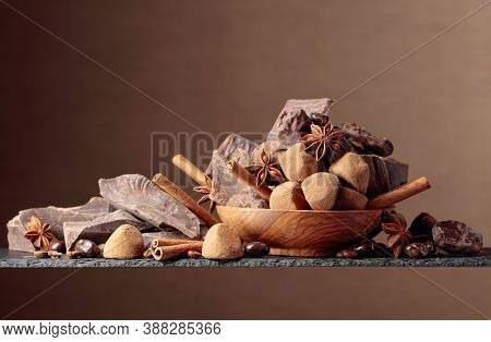 Various Chocolates With Ingredients. In An Old Wooden Bowl Candy, Coffee Beans, Cinnamon, Anise, And