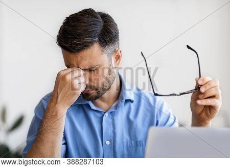 Eyes Pain. Millennial Businessman Massaging Nosebridge, Tired After Working On Laptop Computer In Of