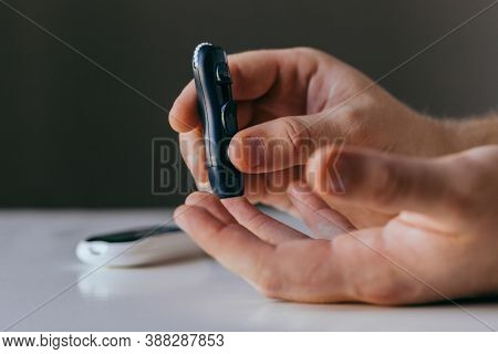 Diabetes, Healthcare - Close Up Of A Man With A Glucometer And A Test Strip Checking Blood Sugar At