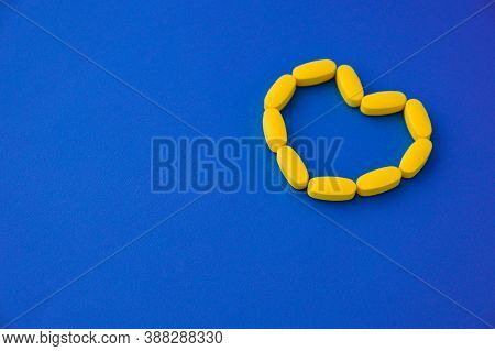 Yellow Pills Health Tablets In Heart Shape Lying On Blue Vivid Surface With Copy Space