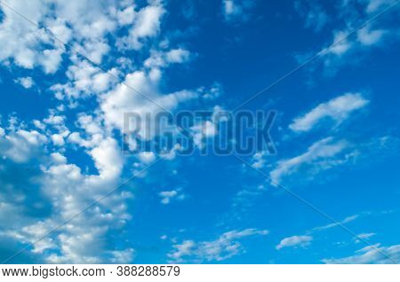 Blue dramatic sky background, white dramatic colorful clouds lit by sunlight. Vast sky landscape panoramic scene, sky background, sunny sky landscape