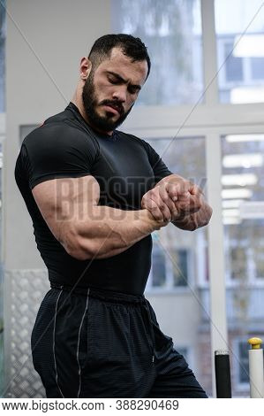 Young Bearded Strong Man In Black Sportswear Showing Muscle Of Biceps During Gym Sport Workout