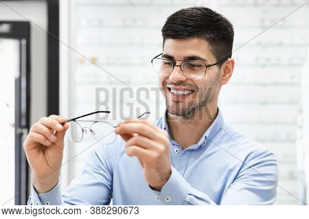 Stylish Eyewear Accessory. Smiling Male Patient With Myopia Trying On New Eyeglasses With Diopters A